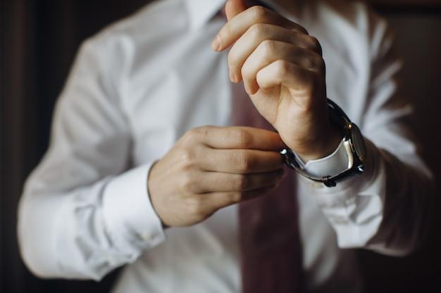 L'homme met sa montre au poignet