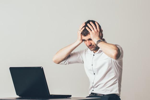 L'homme met ses mains sur sa tête près de son ordinateur portable. les informations sur le moniteur l'ont impressionné
