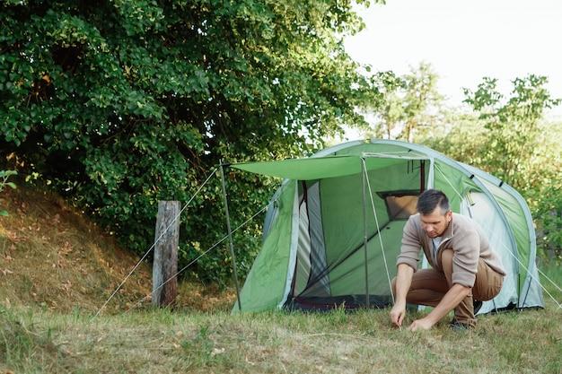 Un homme met une tente dans la forêt.
