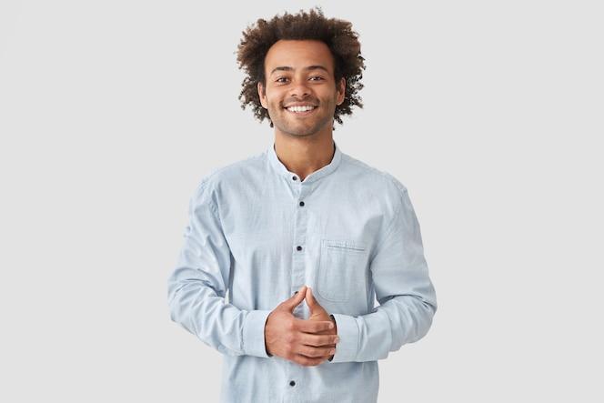 Homme métis attrayant avec un sourire positif, montre des dents blanches, garde les mains sur le ventre, est de bonne humeur, porte une chemise blanche, se réjouit des moments positifs de la vie. concept de personnes et d'émotions