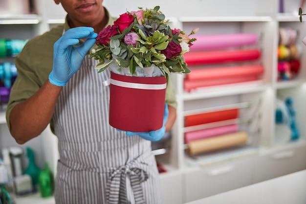 Un homme métis dans un magasin de fleurs enlevant un pétale d'un bouquet de roses