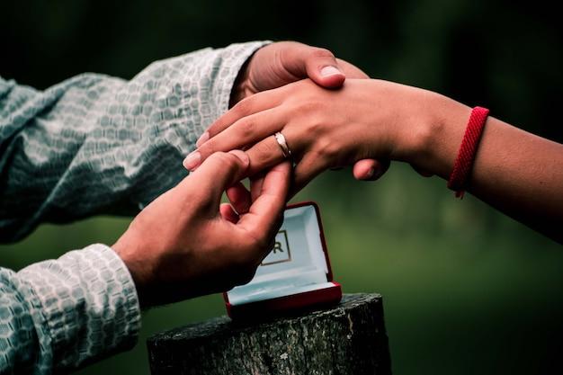 Homme mettant la bague au doigt de la femme