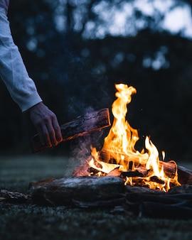 Homme mettant une bûche dans un feu de joie le soir