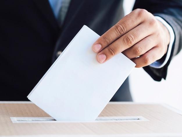 Homme mettant un bulletin de vote dans une boîte close-up