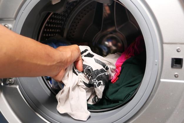 Homme mettant la chemise dans la machine à laver.