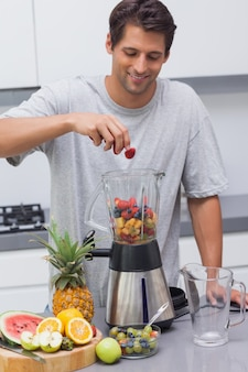 Homme mettant une fraise dans le mélangeur