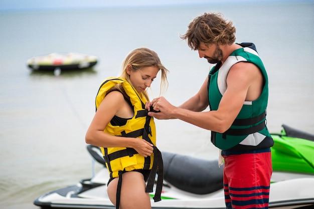 Homme mettant un gilet de sauvetage sur la femme pour monter sur un scooter nautique, vacances d'été, sport actif, sécurité