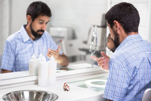 Homme mettant des lentilles de contact dans une clinique d'ophtalmologie.