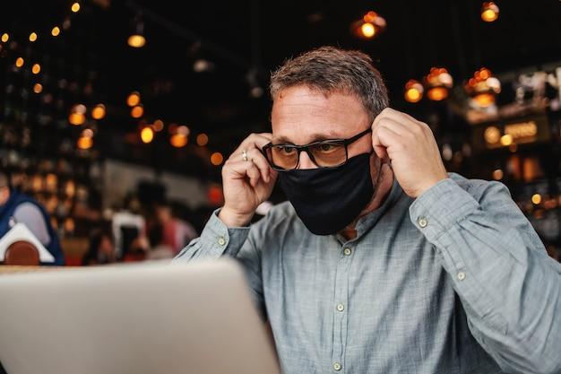 Homme mettant un masque en bar pendant le virus corona.