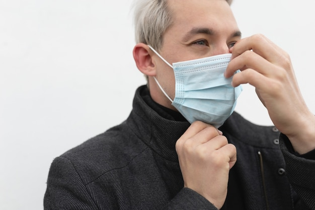 Homme mettant un masque médical isolé