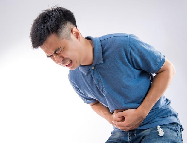 Homme mettant ses mains sur le concept du ventre de maux d'estomac sur fond blanc