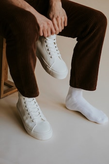 Homme mettant sur shoot studio sneaker