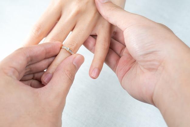 Homme, mettre, bague diamant, sur, femme, main, blanc