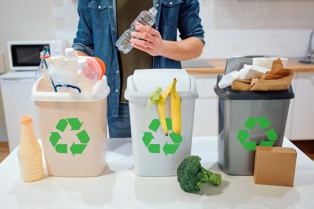 Homme, mettre, bouteille plastique, dans, les, poubelle, dans cuisine