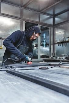 Homme de meulage en acier mécanicien fort et rapide tenant une meuleuse à main