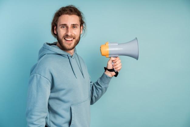 Un homme mignon et barbu se penche sur la caméra, tenant un haut-parleur.