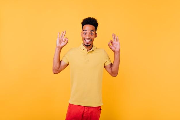 Homme mignon étonné en t-shirt d'été posant. portrait de gars excité aux cheveux noirs.