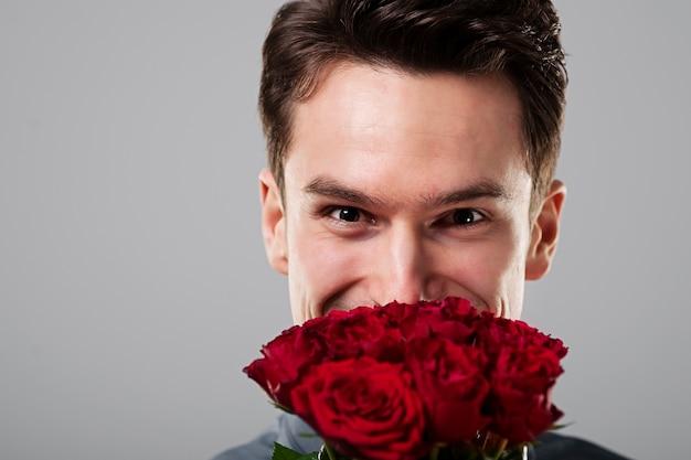 Homme mignon se cachant derrière des fleurs