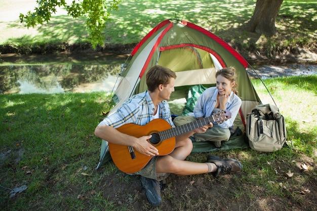 Homme mignon serenading sa petite amie en voyage de camping