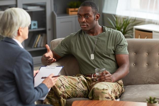 Homme militaire africain assis sur un canapé avec un verre d'eau et consulter un psychologue au bureau