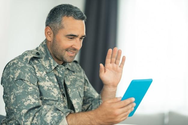 Homme militaire agitant. homme militaire aux cheveux noirs saluant tout en discutant par vidéo avec sa famille sur tablette