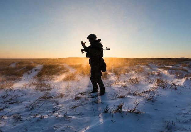 Homme militaire dans un champ enneigé