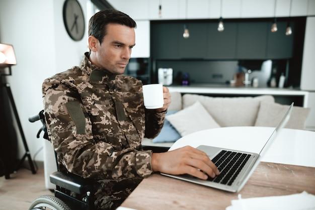 Homme militaire en fauteuil roulant sur ordinateur portable à l'intérieur.