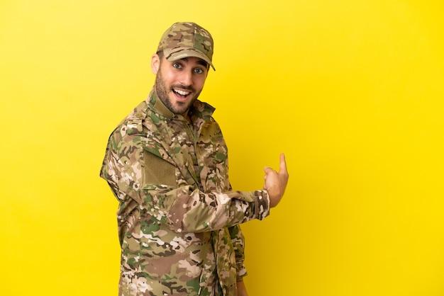 Homme militaire isolé sur fond jaune pointant vers l'arrière
