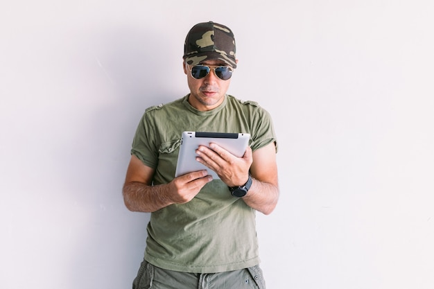 Homme militaire avec des lunettes de soleil à l'aide d'une tablette sur un mur blanc