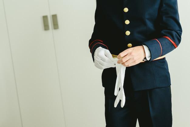 Homme militaire met des gants blancs élégants.