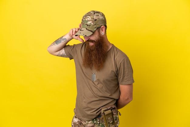 Homme militaire rousse avec dog tag isolé sur fond jaune en riant