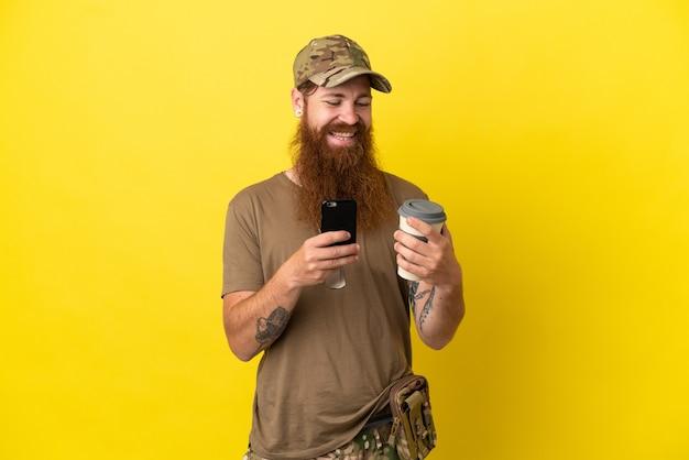 Homme militaire rousse avec dog tag isolé sur fond jaune tenant du café à emporter et un mobile