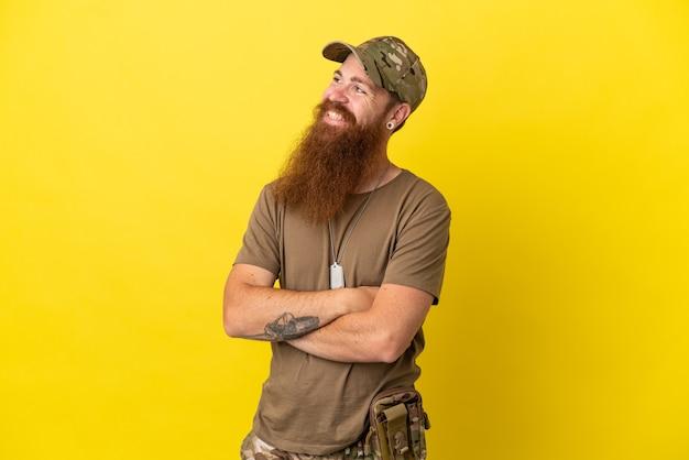 Homme militaire rousse avec étiquette de chien isolé sur fond jaune avec les bras croisés et heureux