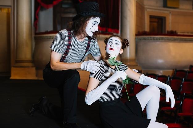 Homme mime artiste en regardant femme mime tenant une rose blanche
