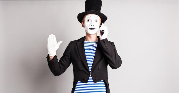 L'homme mime parle sur son téléphone portable. concept du poisson d'avril.