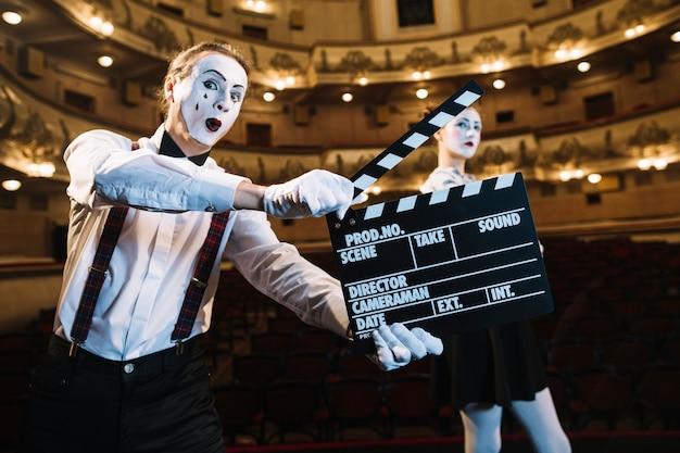 Homme mime tenant un battant devant un artiste mime féminin sur scène
