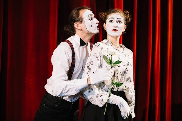Homme mime tenant une rose blanche devant un mime féminin