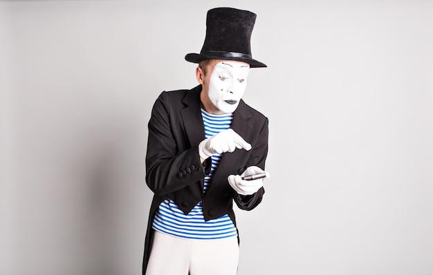 Homme mime tenant un téléphone portable. concept du poisson d'avril.