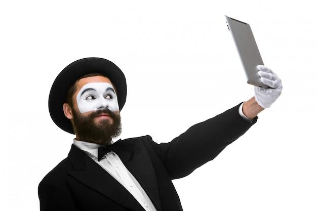 Homme avec un mime de visage travaillant sur un ordinateur portable isolé sur un blanc