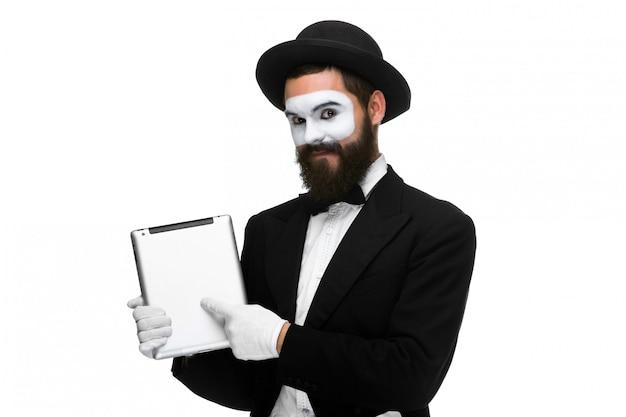 Homme avec un mime de visage travaillant sur ordinateur portable