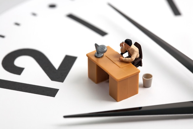 Homme miniature travaillant sur fond d'horloge