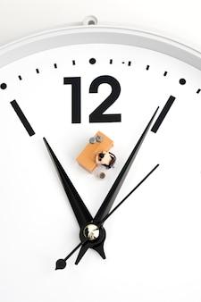 Homme miniature travaillant sur une horloge