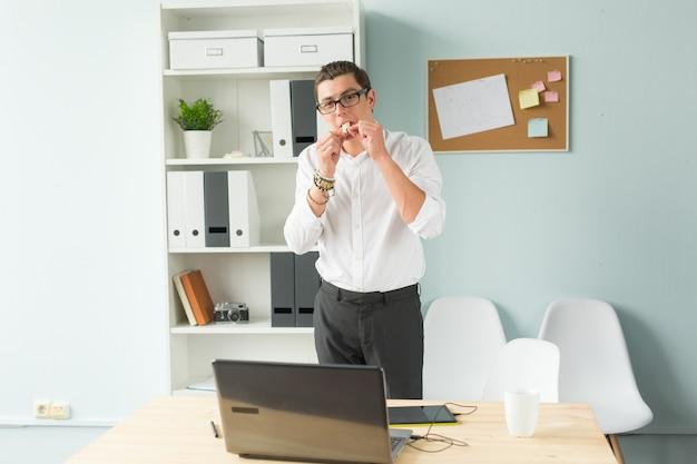 L'homme a mis du chewing-gum dans sa bouche au bureau