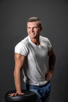Homme de mode attrayant en regardant la caméra en se tenant debout avec une main posée sur une chaise