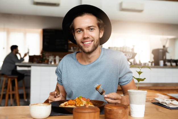 Homme à la mode avec barbe apaisant la faim tout en mangeant seul au restaurant moderne par une journée ensoleillée, manger un repas avec un couteau et une fourchette