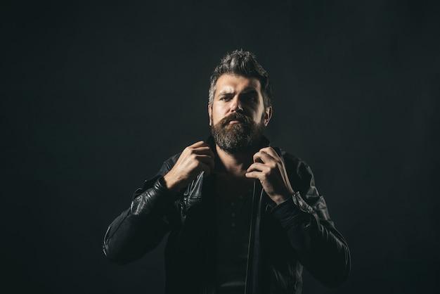 L'homme de la mode. beau portrait de modèle masculin barbu sérieux porter une veste en cuir noir. un homme hipster barbu séduisant répare une veste en cuir à col. mode de saison. copiez l'espace pour faire de la publicité.