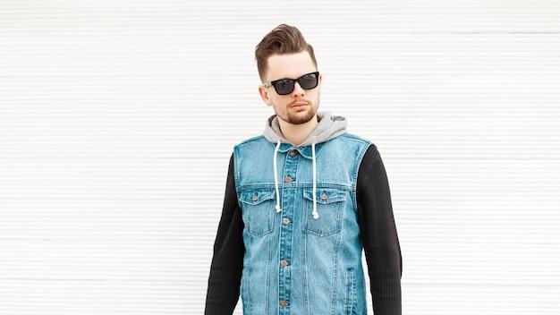 Homme à la mode dans un gilet en denim avec des lunettes de soleil près d'un mur en bois