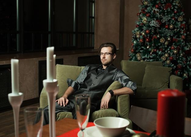 Homme de mode dans un intérieur moderne de luxe, temps de cristmass.