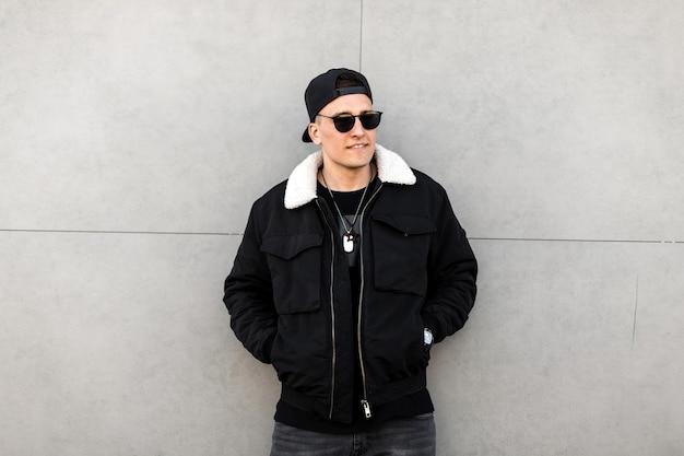 Homme de mode dans des vêtements élégants près d'un mur gris