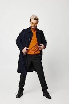 Homme à la mode dans des vêtements sombres, pull orange et modèle de costume de pantalon